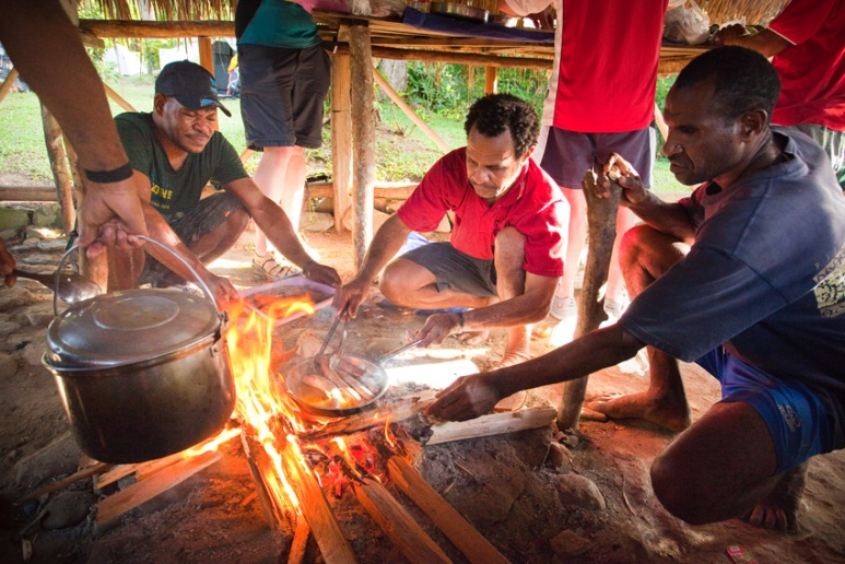 Dinner preparation under the watchful eye of head chef Silva at Hoi Village, Kokoda