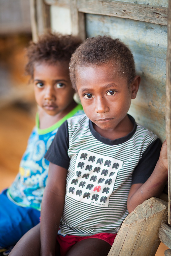Local children sit outside their home of the post war village New Nauro, Kokoda Track, Papua New Guinea.